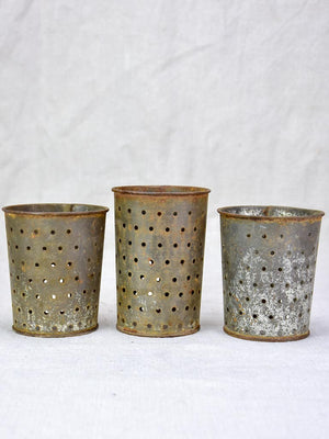 Collection of three tin cheese strainer molds / faisselles