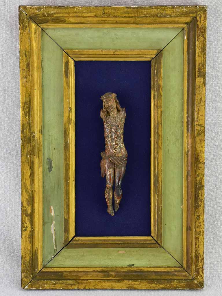 "18th Century sculpted wooden Christ on blue fabric with a green and gold frame 11¾"" x 18½"""