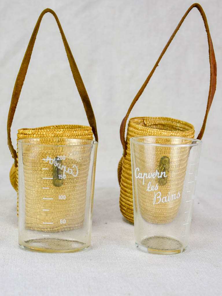 Two mid century French 'verre de cure' glasses in baskets
