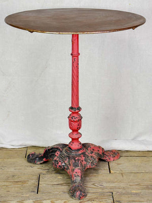 Late nineteenth century French bistro table with red cast iron base