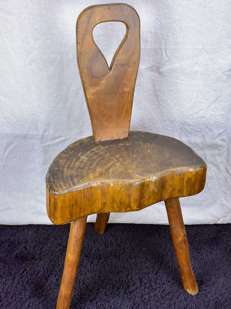 Antique primitive milking chair with three legs and teardrop back
