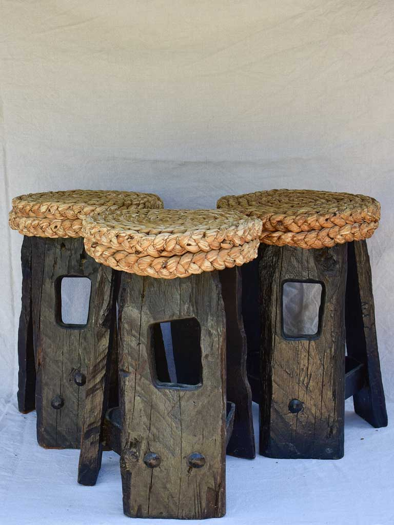Three 1960's stools with woven seats and weighty timber and iron bases