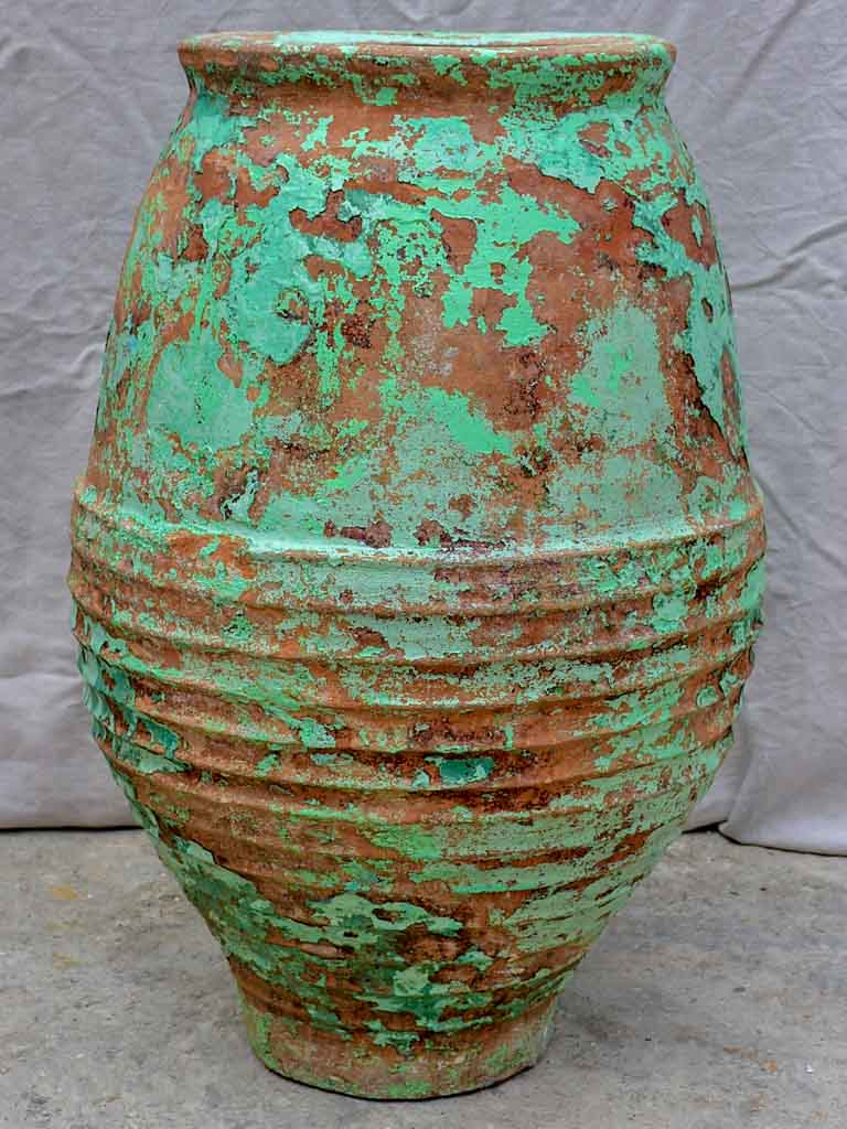 Very large antique Spanish olive oil jar with green patina