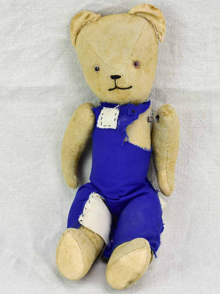 Antique French teddy bear with blue overalls