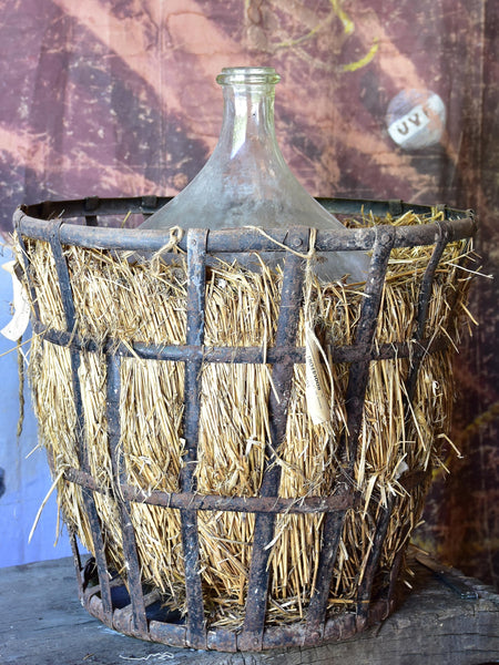 Very large antique French demijohn bottle in hay and crate
