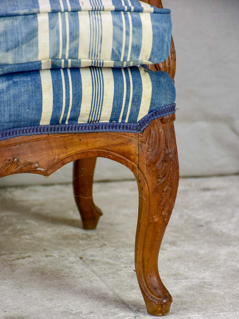 Large antique French Provincial armchair with striped blue and white upholstery walnut frame