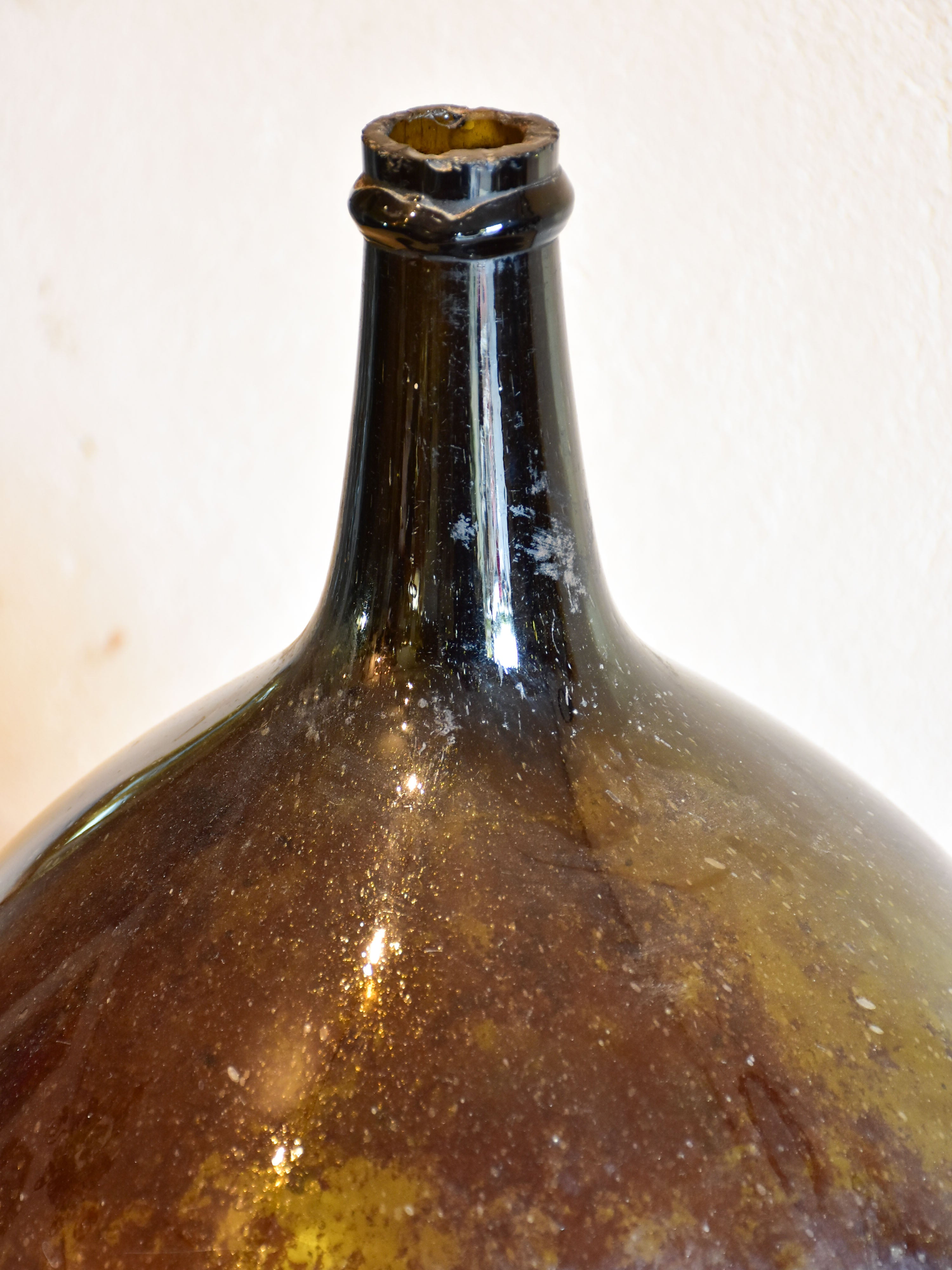Antique demijohn bottle with dark Trinquetaille glass