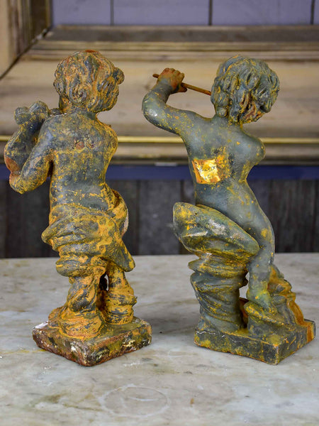 Two antique cast iron cherubs playing musical instruments