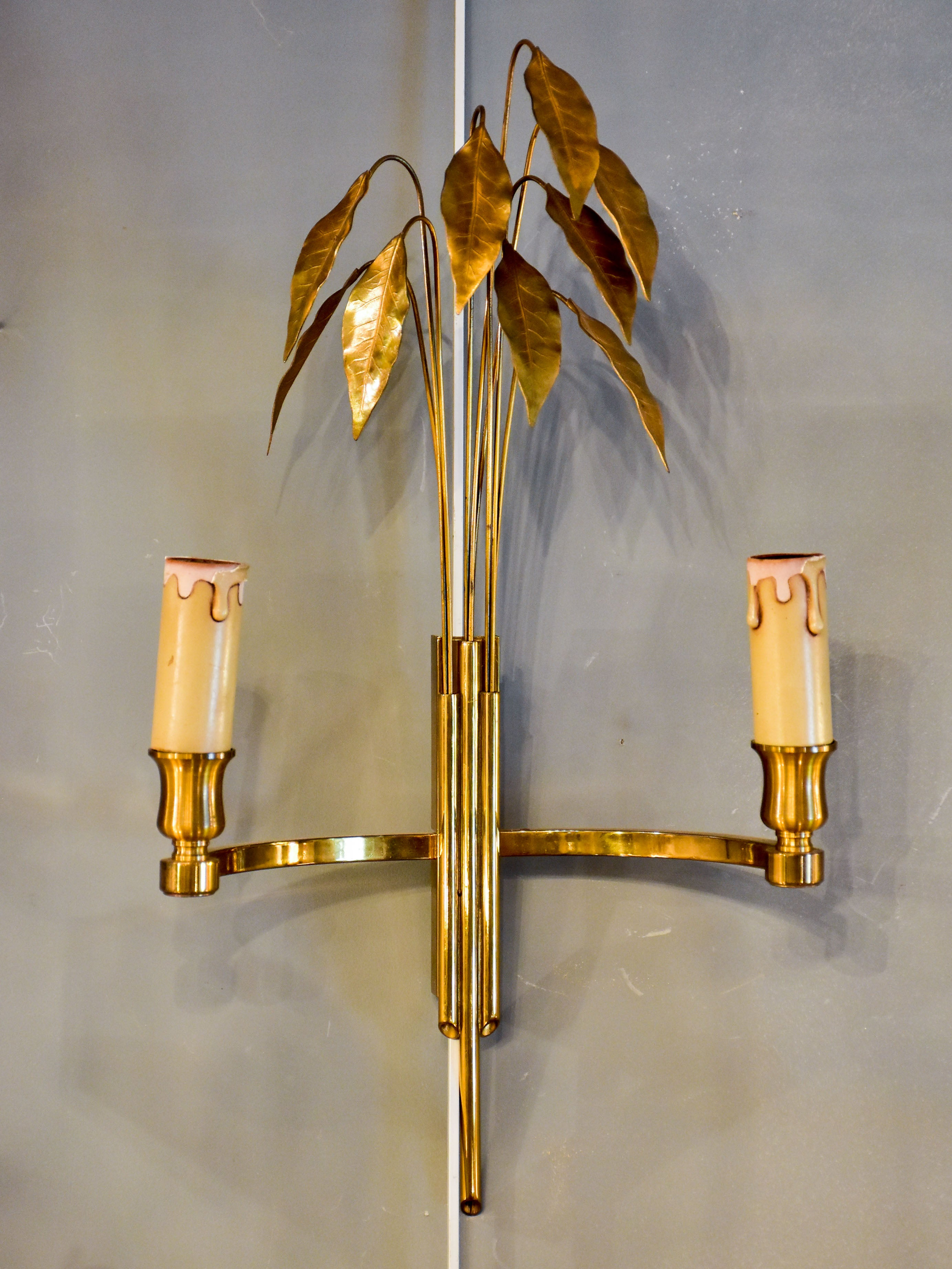 Pair of Maison Charles wall sconces with gold bay leaves