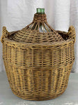 Very large antique French demijohn in a basket