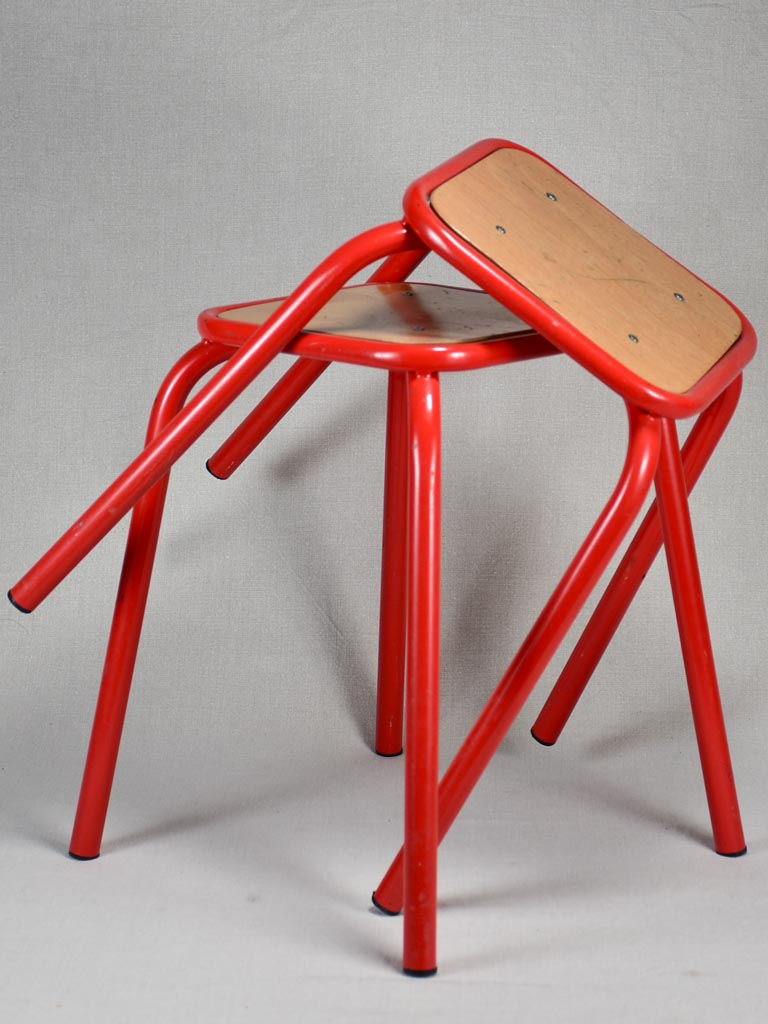 Set of ten red vintage stools from a school