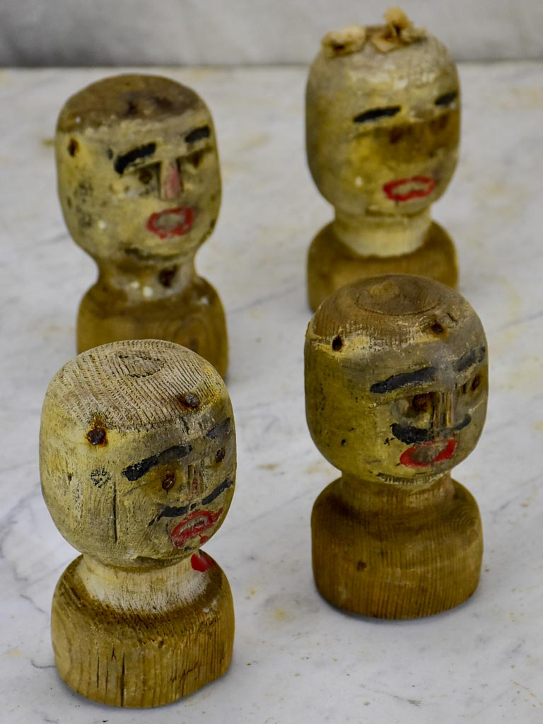 Four antique carved wooden heads from a French game