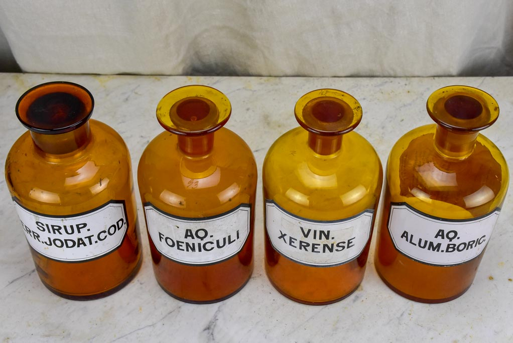 Four antique French apothecary jars with original glass lids - amber