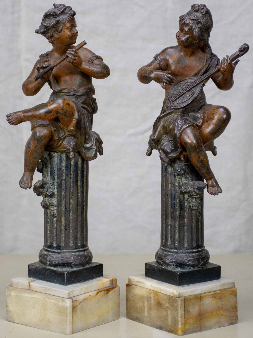 Antique French statues of angels playing music
