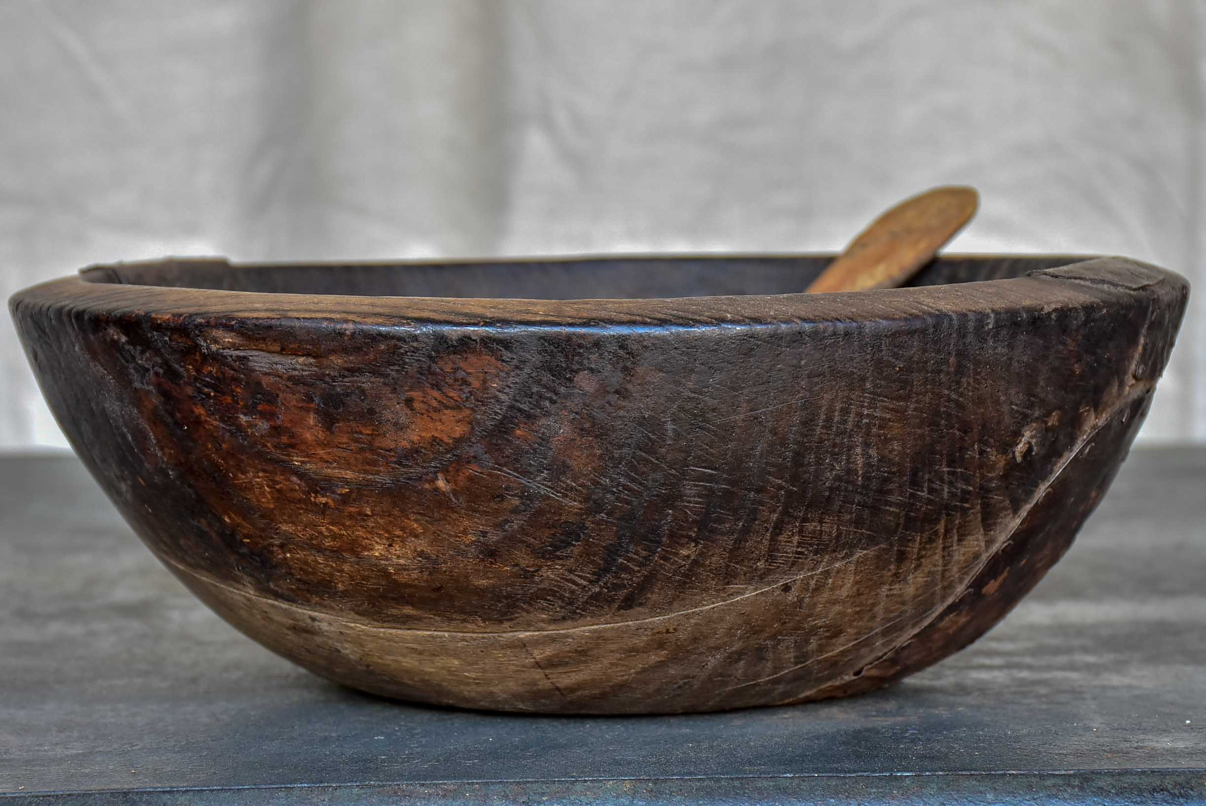 An antique French wooden bowl with repairs