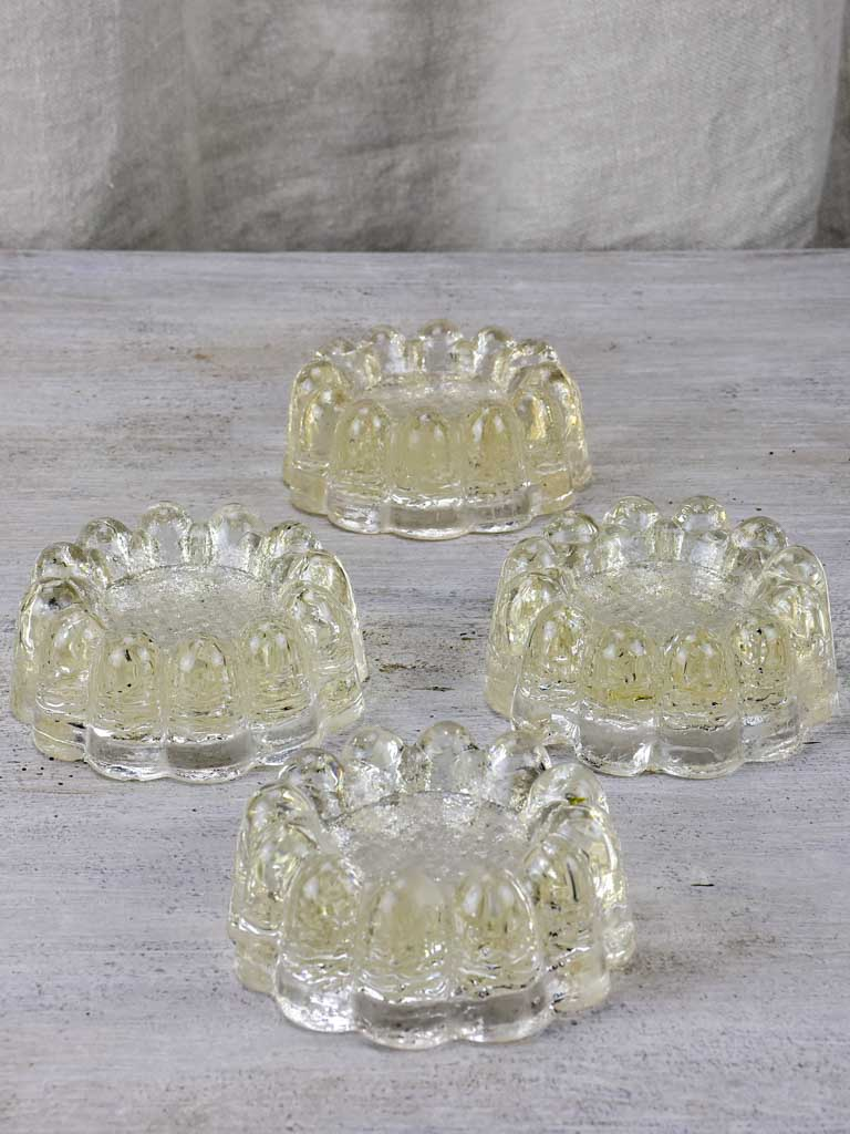 Four antique French glass table risers