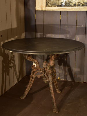 Large round table with cast iron legs and slate table top