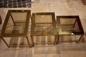 Set of three 1960s nesting tables in brass and tinted glass