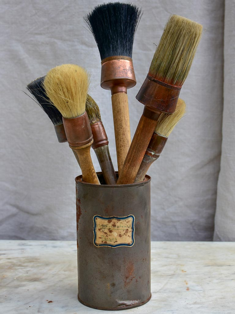 Collection of vintage paint brushes in a tin