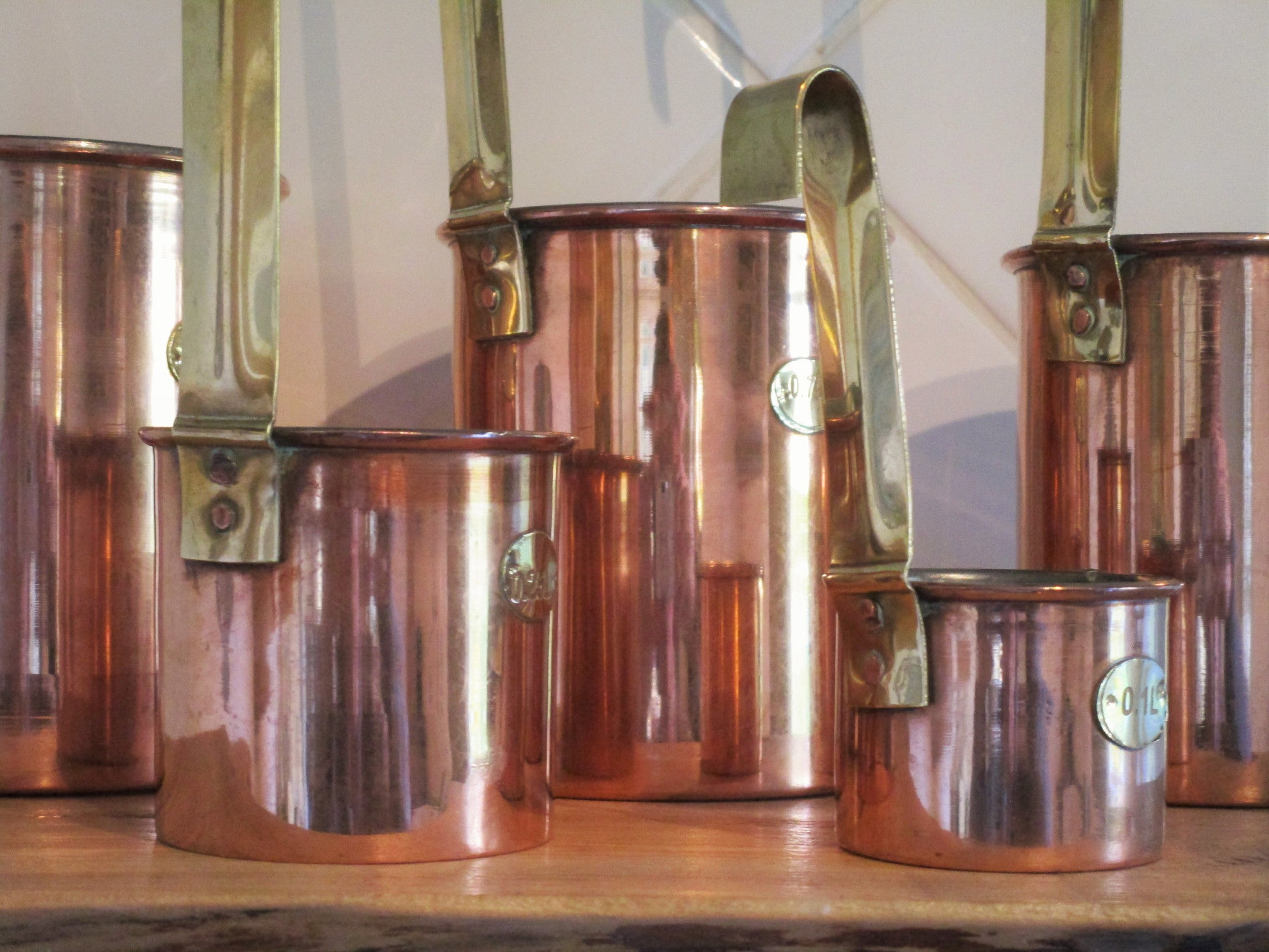 Set of five chef's copper measuring cups polished