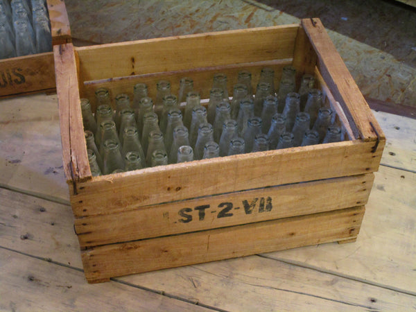 A rustic French fruit box filled with vintage glass bottles
