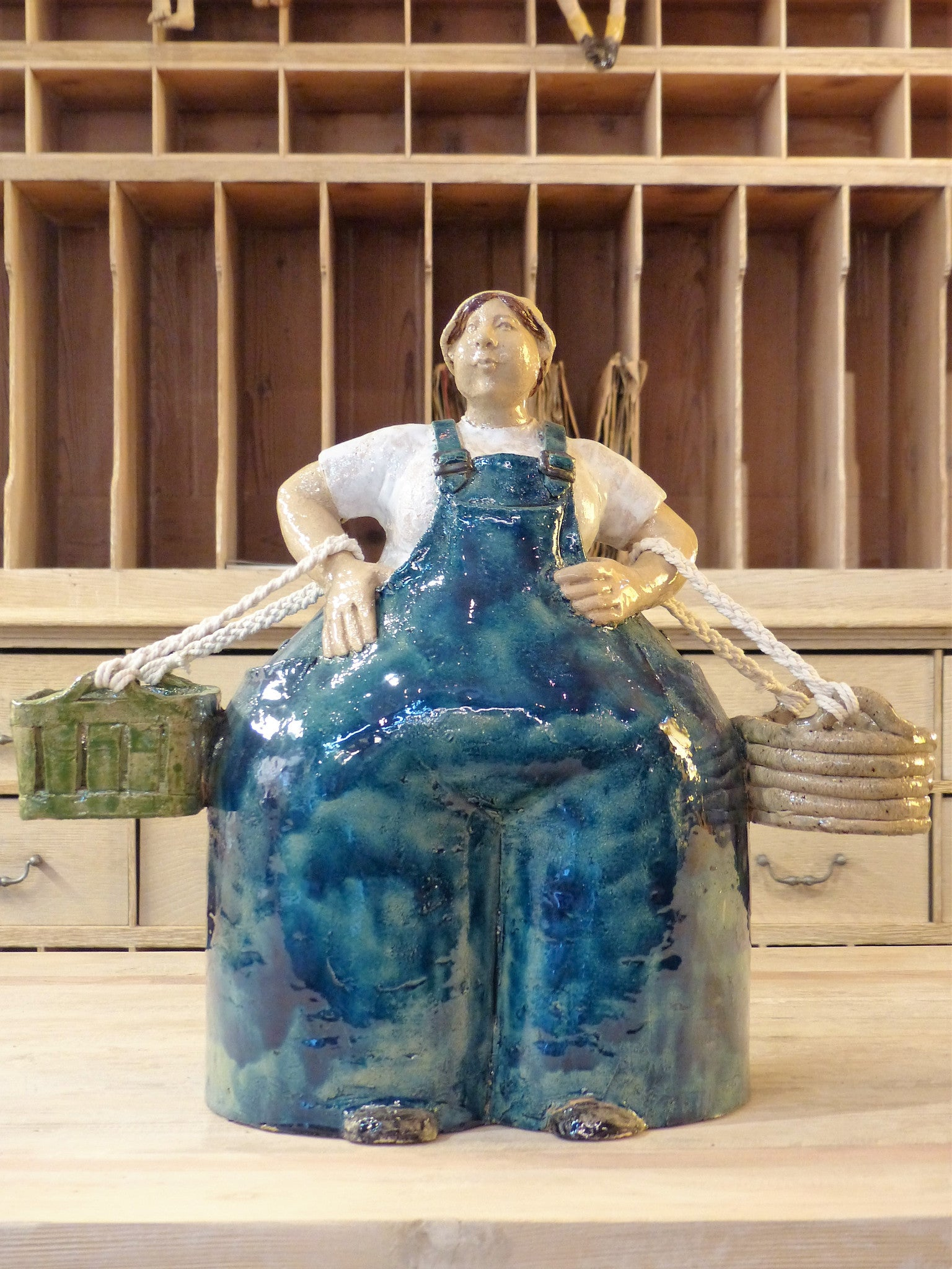 """œMadame agriculteur""? sculpture with two baskets and blue overalls"