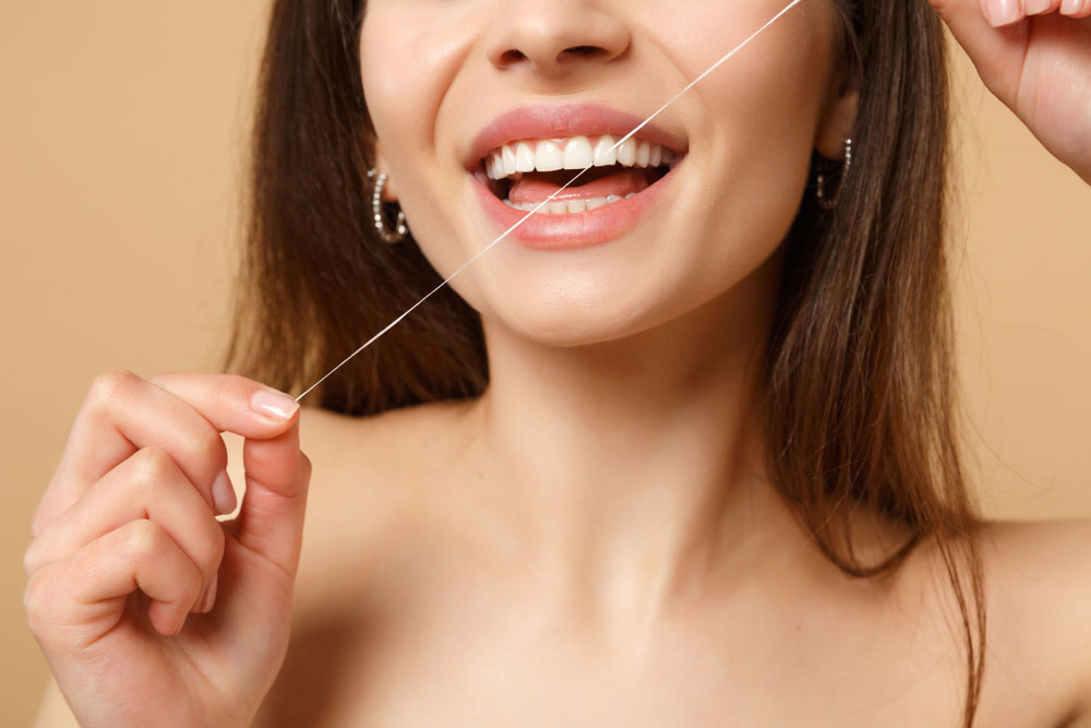 string floss in woman's mouth