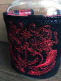 Image of a handmade and pirate themed mug or mason jar cozy. It features bold red and black woven jacquard stripes on one side and a red mermaid pirate crest embroidered on black faux alligator leather on the reverse.