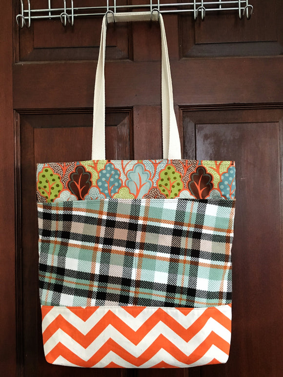 Image of an extra large handmade tote bag made from orange and white cotton canvas, mint green, deep brown, and rich orange Anne of Green gables inspired woven tartan, and camel line, it features generous external and internal pockets and woven cotton webbing straps.