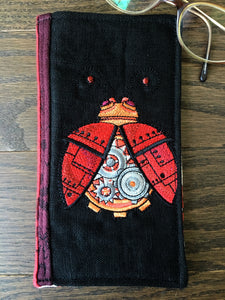 Image of an elegant and geeky handmade glasses case sewn from Oscha Slings ladybird wrap scrap in deep reds, burgundy, and black. It features a hip steampunk ladybug embroidery design and quilted woven jacquard. The perfect geek gift.
