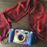 Image of a handmade scarf style camera or binoculars strap. It features crimson red and black woven wrap scraps by Oscha Slings and easy to change out rings and clasps.