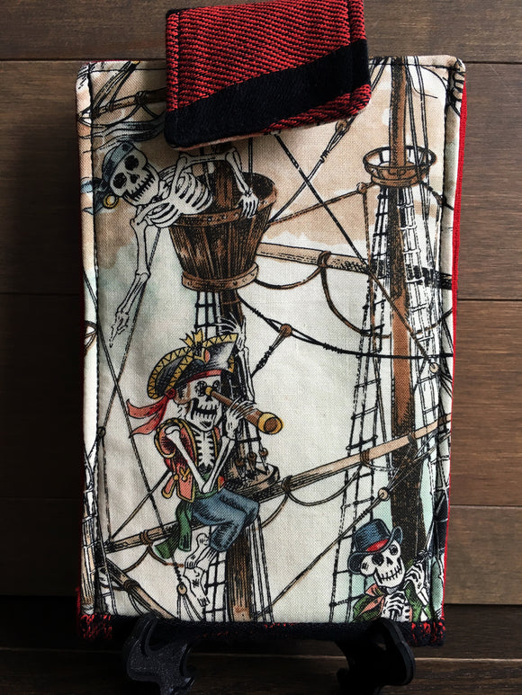 Image of a handmade and pirate themed phone pouch. It features skelewag fabric from Alexander Henry, bold red and black skull and crossbones woven jacquard fabric, an internal card pocket, and a belt or purse clip.