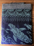 Image of a handmade blue and turquoise padded tablet case made from Oscha Slings Selkie Luminescence wrap scraps. It features houndstooth wool tweed and woven jacquard with seals, mermaids, and selkies.