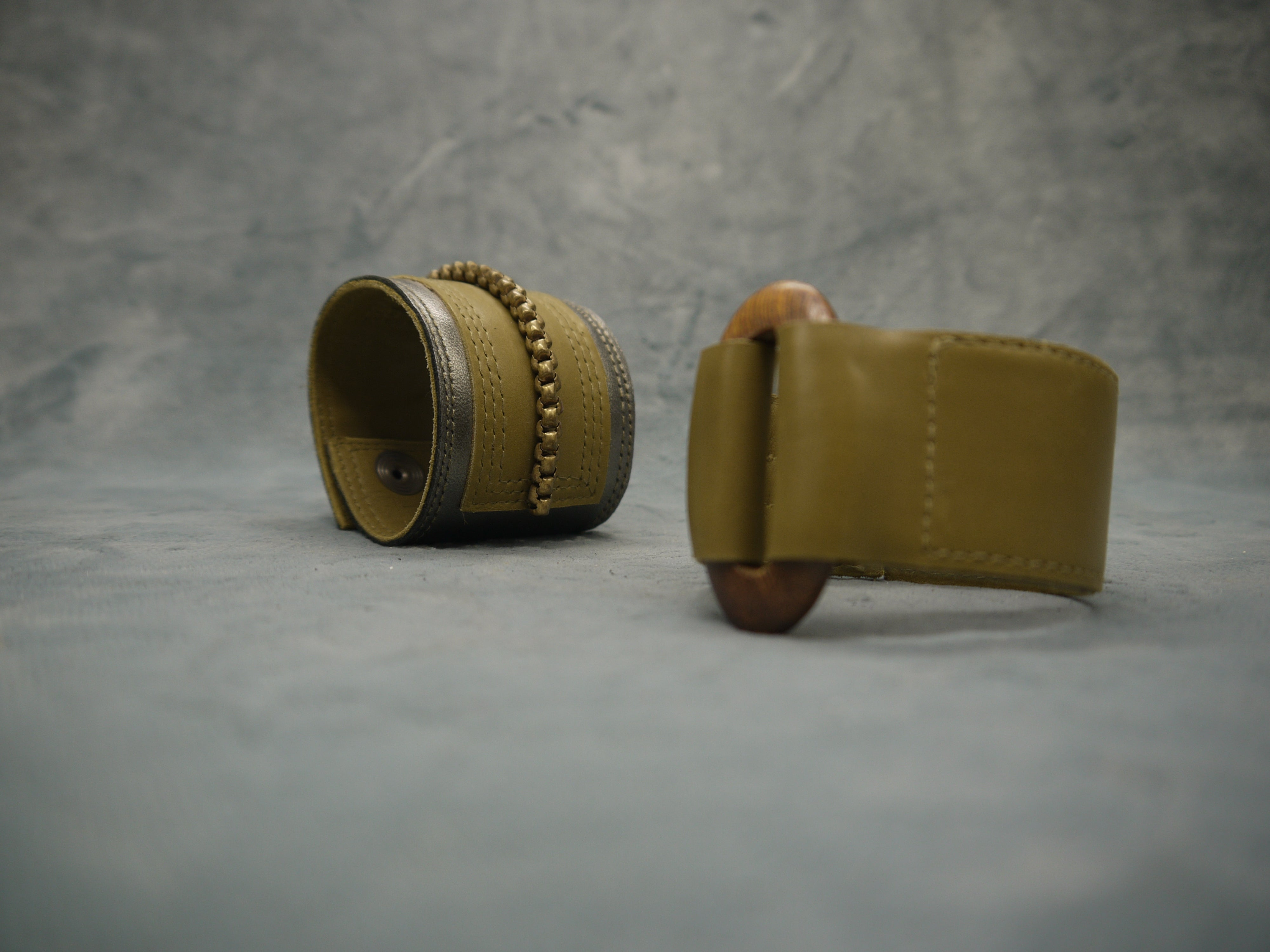 Leather cuff in soft Italian leather in olive green. Central oval element in wood units the two sections on the leather cuff. IN the background the Gunmetal/Olive grey cuff with brass central chain and repeat stitch detail is shown as complimentary accessory