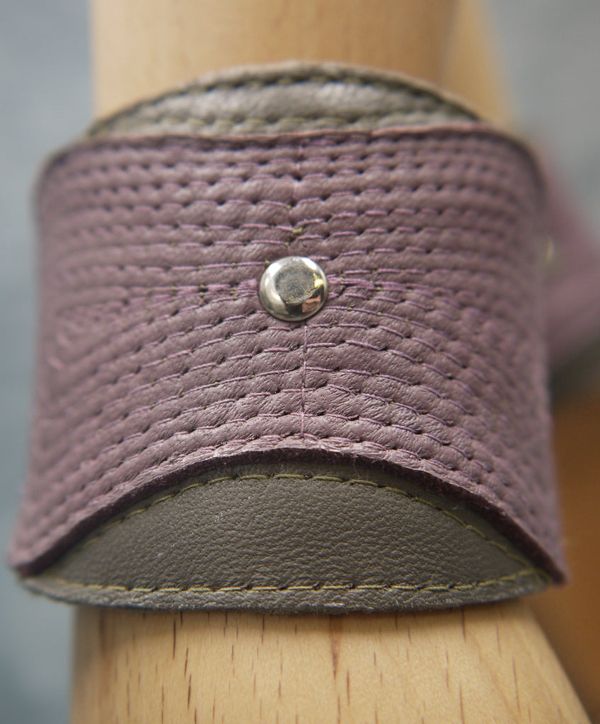 Leather cuff in olive green and smokey lilac. The central smokey lilac lozenge shape section has a concentrical stitching detail.There is a central steel circle as a focal point where the stitching ends. Close-Up Image