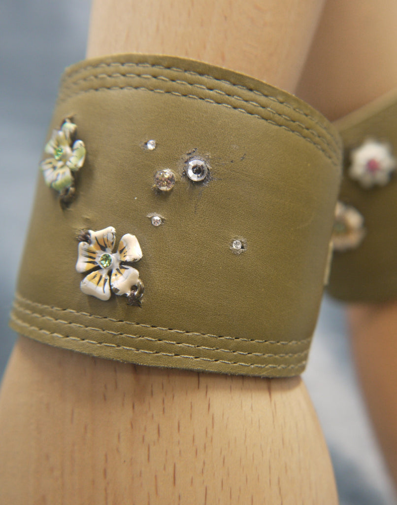 Leather Cuff in Moss green nappa, with repeat stitch edge detail . Set with two enamelled flowers on pale apricot and pale green. Also set with clear crystals which create a dew drop effect
