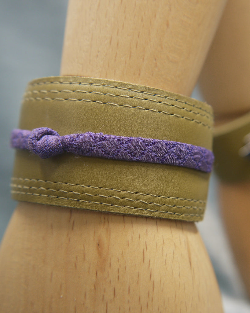 Olive green slimline Italian leather cuff with royal purple slim silk  knot central on the cuff. The cugff has elegant repeat stitch detail around the edges. Close-Up Image