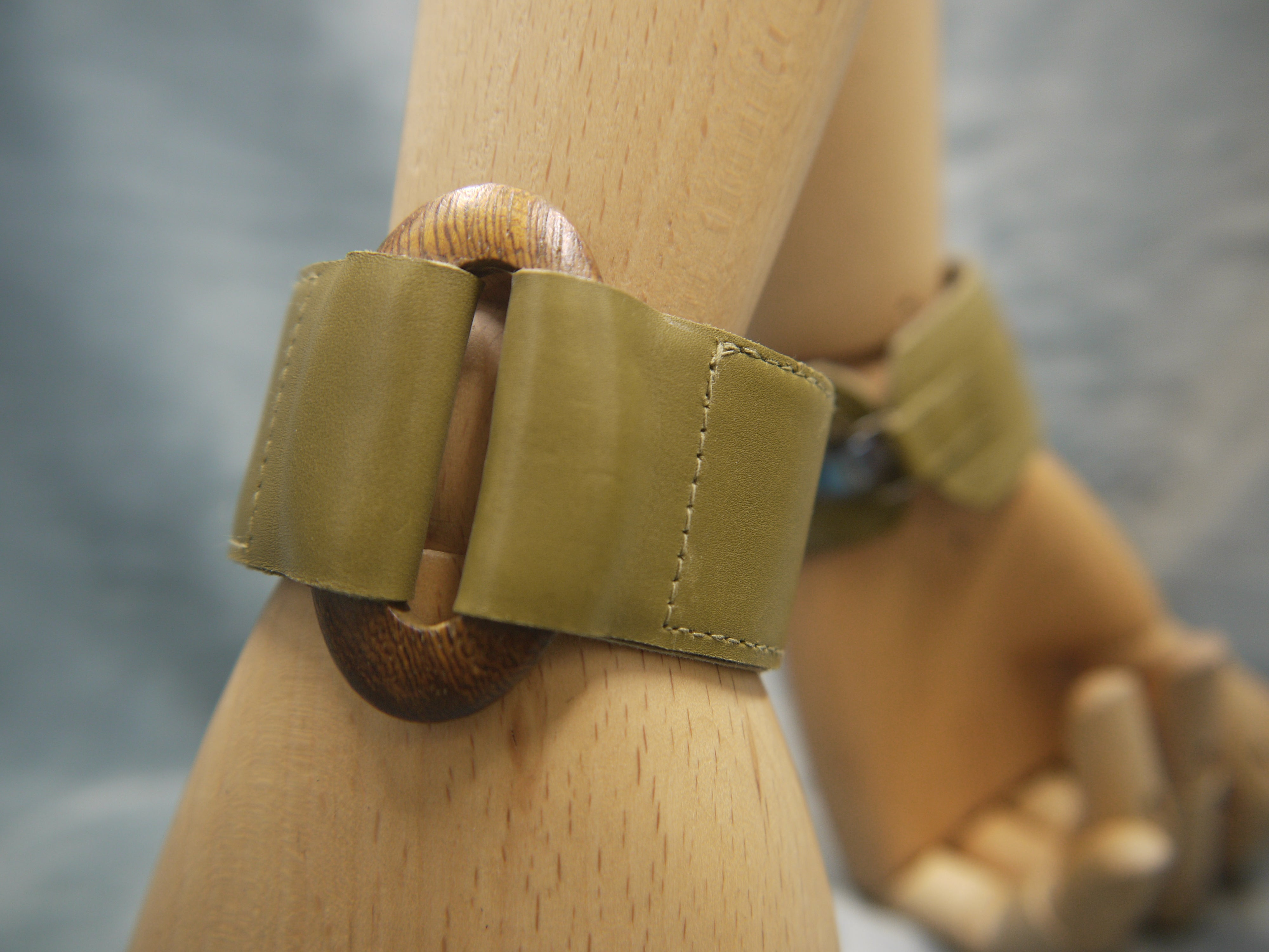 Leather cuff in soft Italian leather in olive green. Central oval element in wood units the two sections on the leather cuff