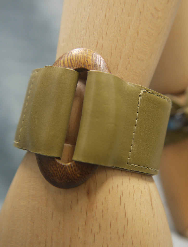 Leather cuff in soft Italian leather in olive green. Central oval element in wood units the two sections on the leather cuff. Close up image