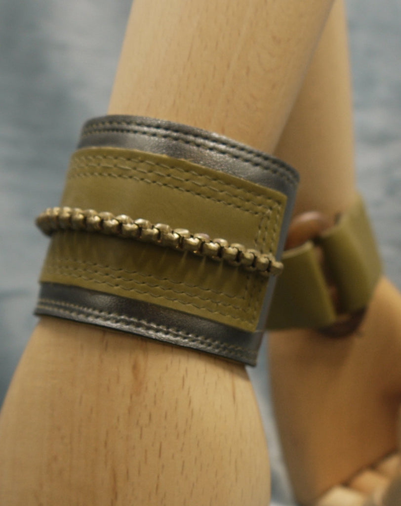 Leather cuff in Gunmetal metallic leather and moss green leather central rectangle which has repeat stich detail which frames the rectangle. A central brass chain is the focal point of the cuff, sewn central across the moss green rectangle.