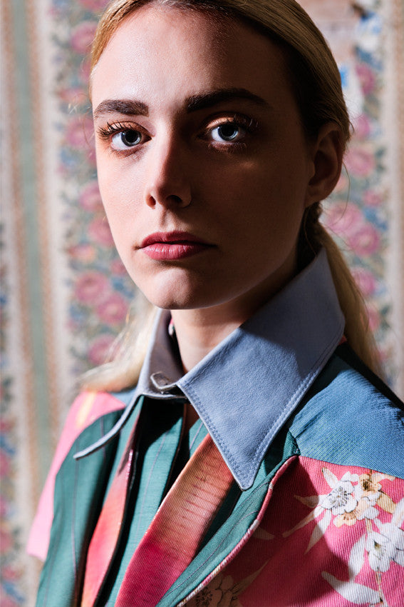 Model Wallflowers photoshoot wears Pale blue leather shirt collar over Leather Degradè rose coloured leather undone bow-tie. Close-Up image