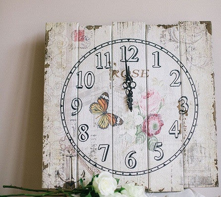 A Rustic distressed floral print wooden plank clock .
