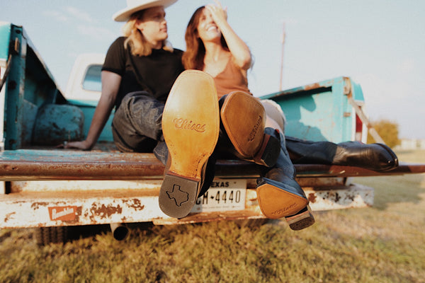 man and woman in truck bed with cowboy boots on