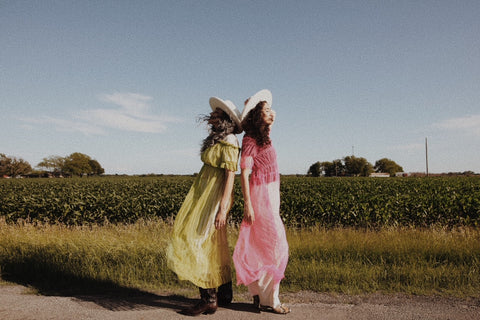 two girls standing by a field with pink and green dresses on