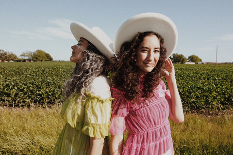 two girls with hats on in a field