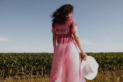 girl standing in field with pink dress on holding a hat