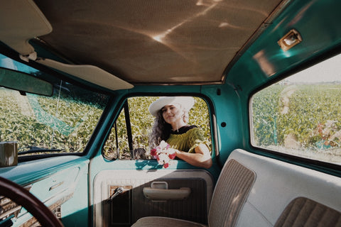 girl in truck window with hat on