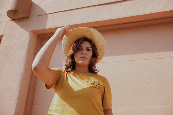 women in yellow tee with hat