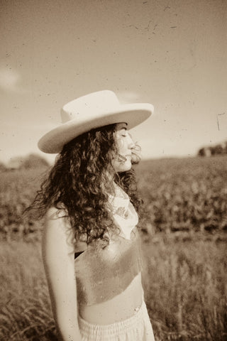 girl standing in field with hat on
