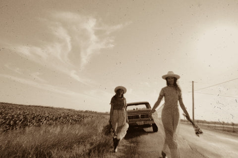 two girls walking towards camera with a truck in the background
